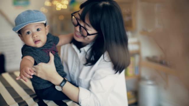 若い女性の家に男の子の赤ちゃんと遊ぶ - 帽子点の映像素材/bロール