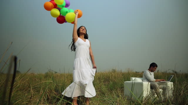 Young woman playing with balloons in the forest