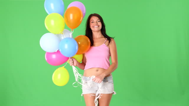 Young woman playing with balloons