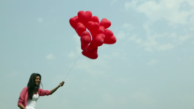 young woman playing with balloons  - gruppe von gegenständen stock-videos und b-roll-filmmaterial