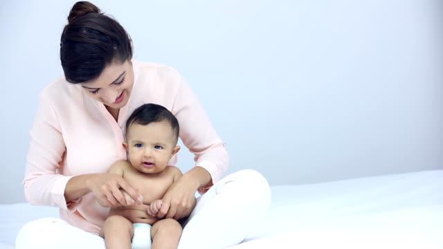 young woman playing with her baby at home, delhi, india - korslagda ben bildbanksvideor och videomaterial från bakom kulisserna