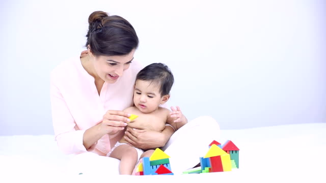 stockvideo's en b-roll-footage met young woman playing with her baby at home, delhi, india - in kleermakerszit