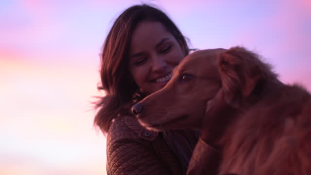 CU Young woman playing with her dog at sunset.