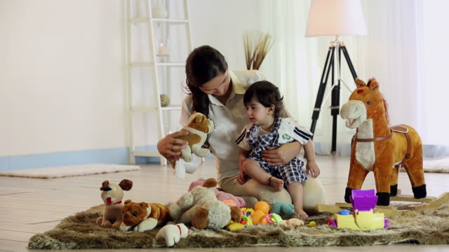 young woman playing with her son in the home - soft toy stock videos & royalty-free footage