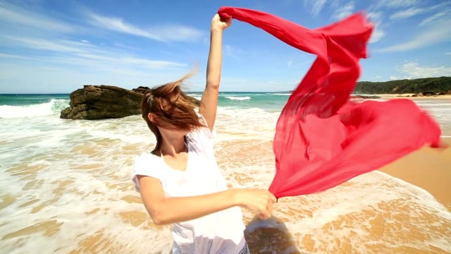 Young woman playing with sarong on the beach
