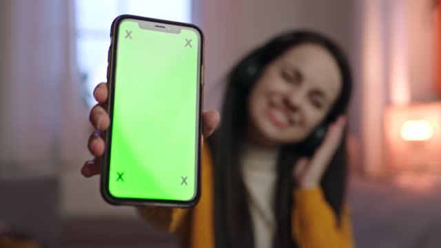 ms young donna che punta con un dito su uno schermo con chiave cromatica del suo smartphone - mostrare video stock e b–roll