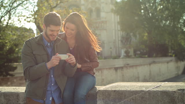 Young woman poses for photo with Notre Dame de Paris and looks at smartphone with boyfriend on Petit Pont.