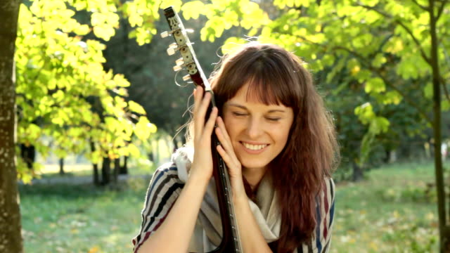 Young woman posing in park, holding guitar, smiling, flirting outdoors.
