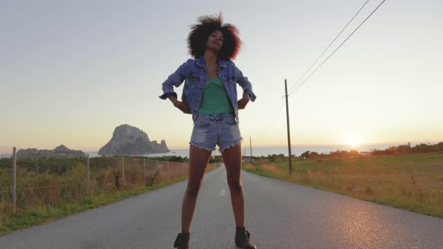 vídeos de stock e filmes b-roll de young woman posing on road at sunset - jaqueta jeans