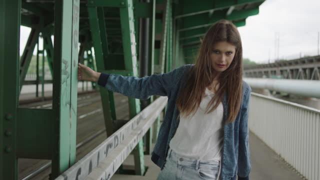 Young woman posing under bridge. holding steel pillar