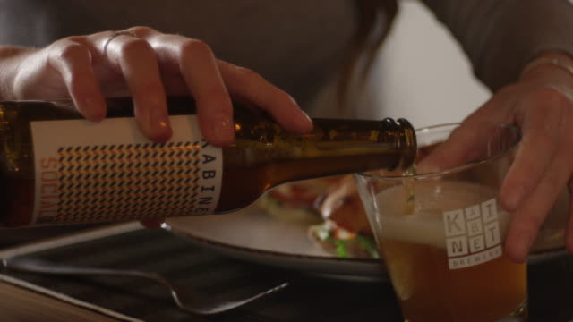 Young Woman Pouring Beer Into Glass 4K slow motion