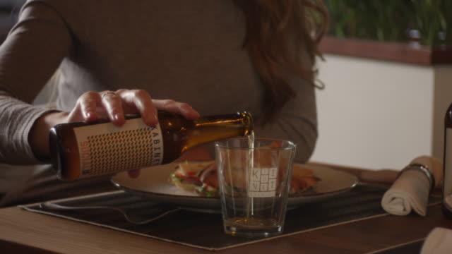 vídeos y material grabado en eventos de stock de joven mujer vierte cerveza en vidrio 4k lenta - beer mug