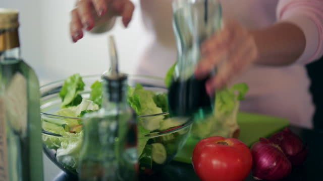 cu young woman pouring dressing on salad - salad dressing stock videos & royalty-free footage