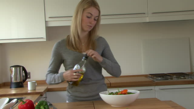 vídeos y material grabado en eventos de stock de young woman pouring salad dressing onto salad; uk - ensalada