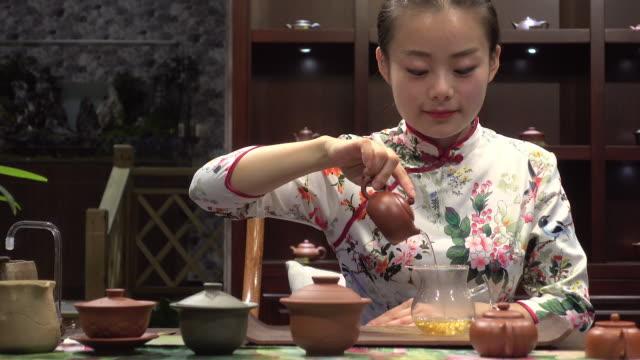 vídeos y material grabado en eventos de stock de young woman pouring tea - diseño floral