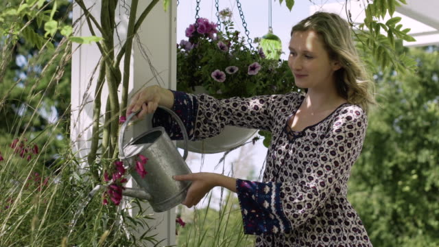 young woman pouring water onto plants - bluse stock-videos und b-roll-filmmaterial