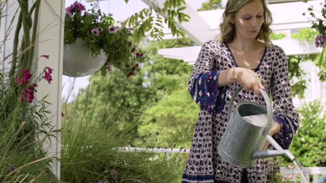 vídeos de stock, filmes e b-roll de young woman pouring water onto plants - regando