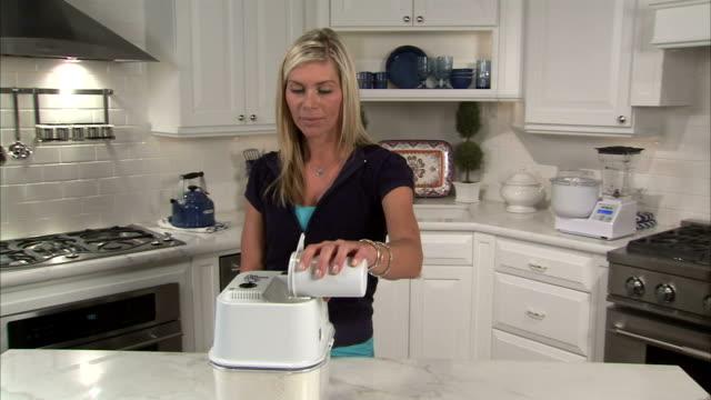 stockvideo's en b-roll-footage met ms pan young woman pouring wheat into wheat grinder in kitchen / salt lake city, utah, usa - volkoren