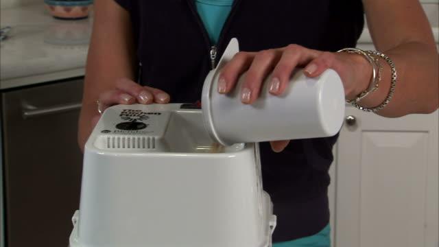 ms tu td young woman pouring wheat into wheat grinder in kitchen / salt lake city, utah, usa - korta ärmar bildbanksvideor och videomaterial från bakom kulisserna