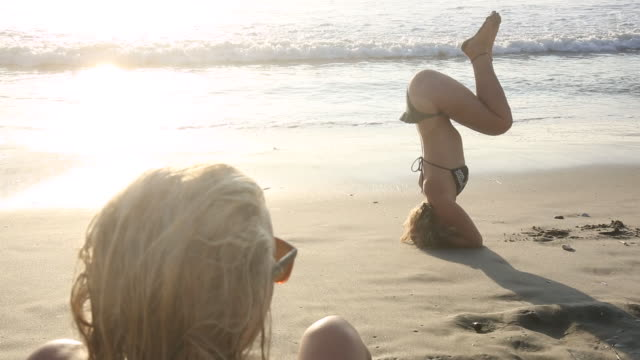 Young woman practices headstand/scorpion maneuver on beach