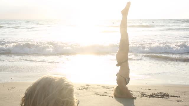 vidéos et rushes de young woman practices headstand/scorpion maneuver on beach - paradisiaque