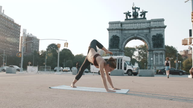 A young woman practices Yoga at Grand Army Plaza in Brooklyn, NYC - 4k - slow motion