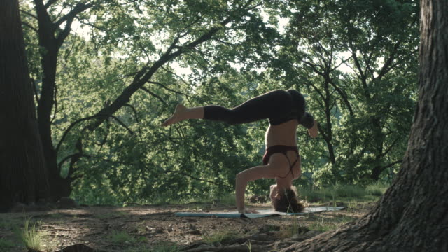 A young woman practices Yoga early in the morning in nature - 4k - slow motion