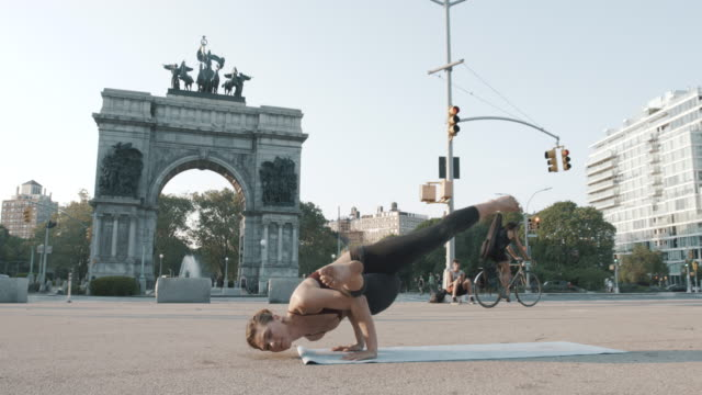 vídeos de stock, filmes e b-roll de a young woman practices yoga in the streets of brooklyn, new york city - flushing meadows corona park