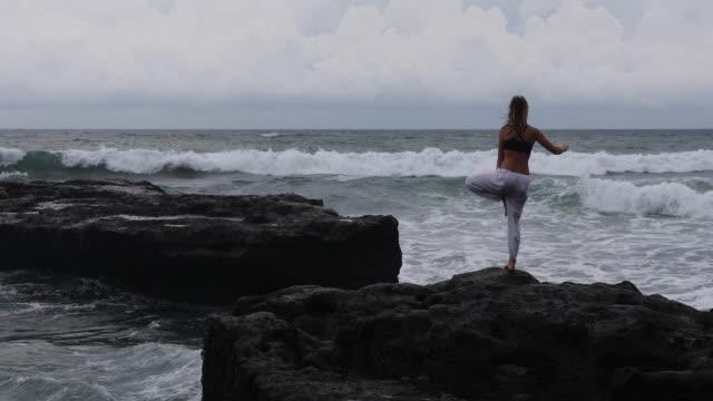 vídeos de stock, filmes e b-roll de young woman practices yoga moves on cliff above sea - pose de arvore