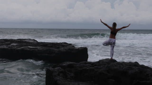 Young woman practices yoga moves on cliff above sea