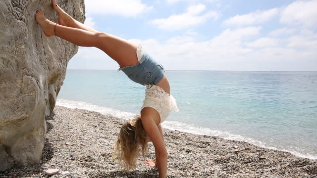 Young woman practices yoga/stretching position by beach edge