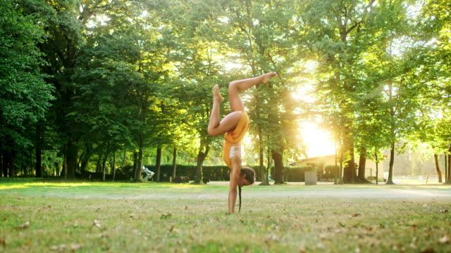 vídeos de stock e filmes b-roll de ms young woman practicing handstand pose in sunny, idyllic park - descalço