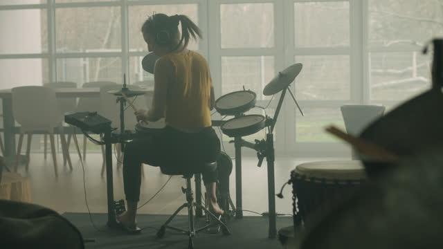 junge frau übt auf elektronischen trommeln in ihrem wohnzimmer - popmusiker stock-videos und b-roll-filmmaterial