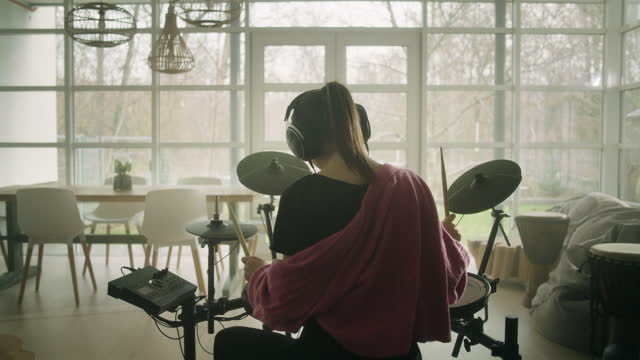 young woman practicing on electronic drums in her living room - drummer stock videos & royalty-free footage