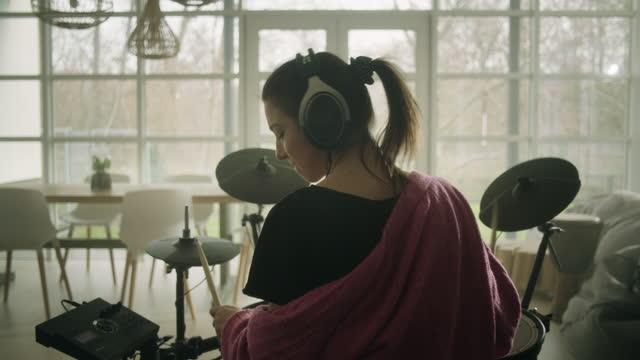 junge frau übt auf elektronischen trommeln in ihrem wohnzimmer - arts culture and entertainment stock-videos und b-roll-filmmaterial