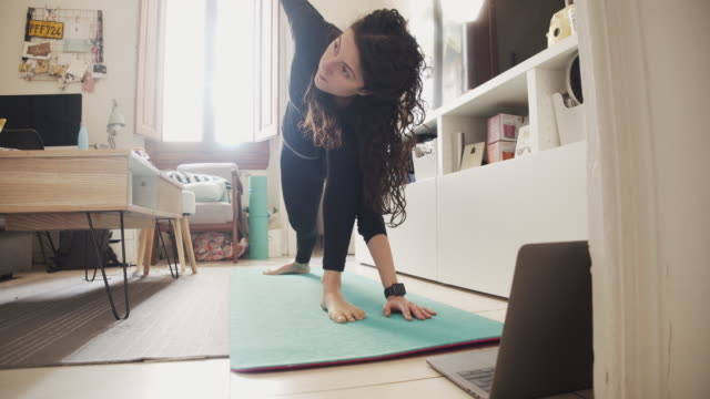 young woman practicing yoga at home - quarantena video stock e b–roll