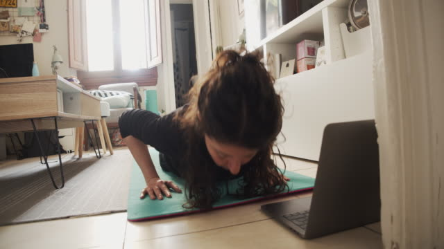 young woman practicing yoga at home - instructor stock videos & royalty-free footage