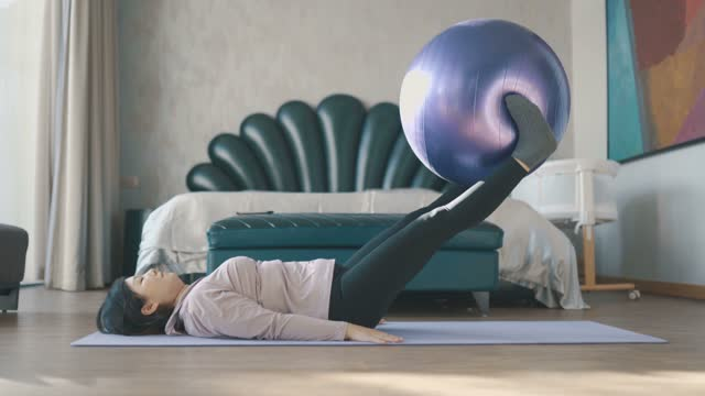 young woman practicing yoga at home - fitness ball stock videos & royalty-free footage