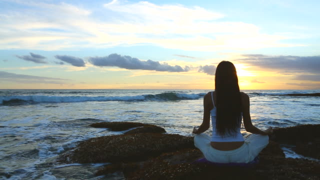 young woman practicing yoga at sunset near seaside - bali stock videos & royalty-free footage