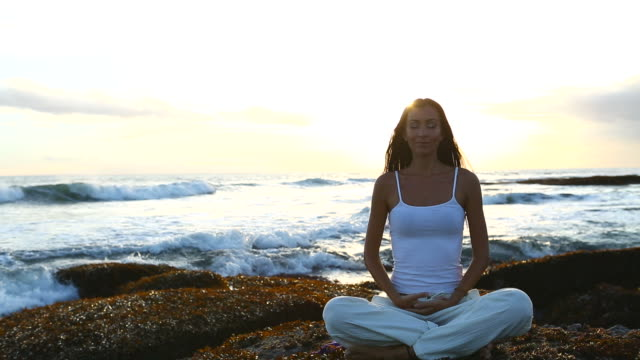 Young woman practicing yoga at sunset near seaside