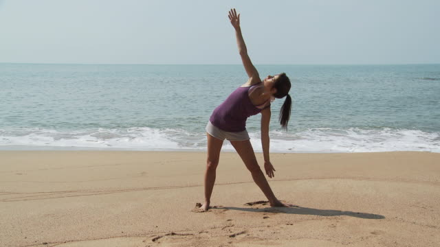 Young woman practicing yoga by the sea