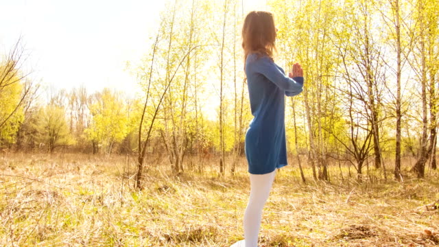 Young woman practicing yoga in a spring forest.