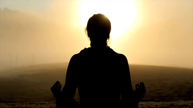 Young woman practicing yoga in sunrise