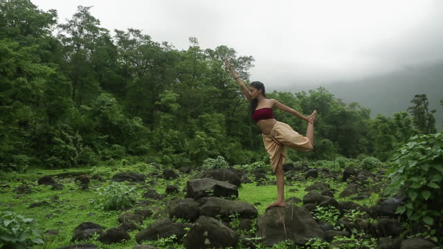 Young woman practicing yoga in the forest, Malshej Ghat, Maharashtra, India