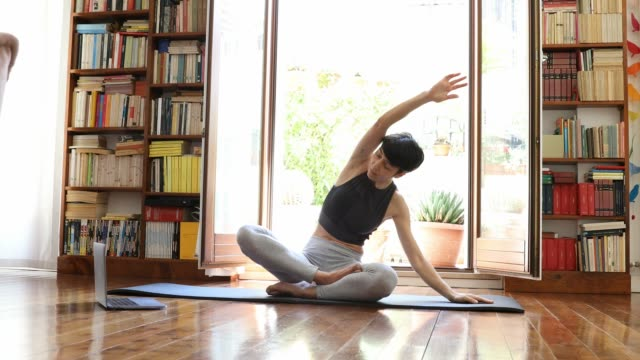 young woman practicing yoga in video call from home - exercise class stock videos & royalty-free footage