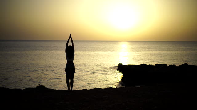 young woman practicing yoga near the beach silhouetted by sunset - human limb stock videos & royalty-free footage