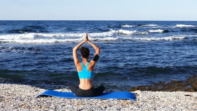 vídeos y material grabado en eventos de stock de 4k joven practicando yoga en la playa - con las piernas cruzadas