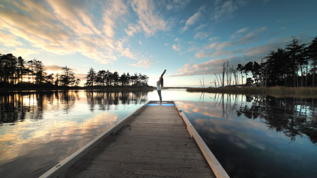Young woman practicing yoga on dock of lake, at sunset, Oregon