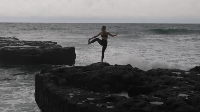 Junge Frau praktiziert Yoga bewegt sich über dem Ozean