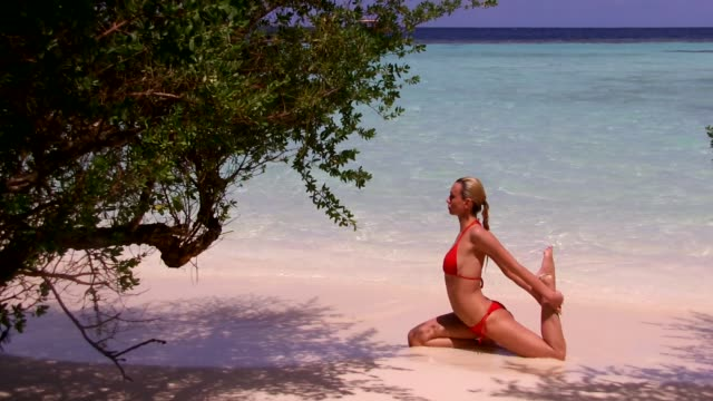 Young Woman Practising Yoga Exercise On Tropical Beach Wearing Bikini